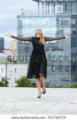 Vogue plus size model wearing black dress posing over urban background. Fashion shot.