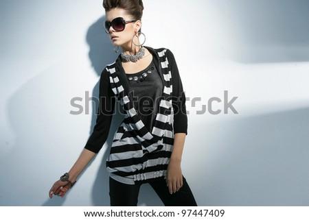 Vogue style fashion model wearing modern sunglasses posing on light background - stock photo