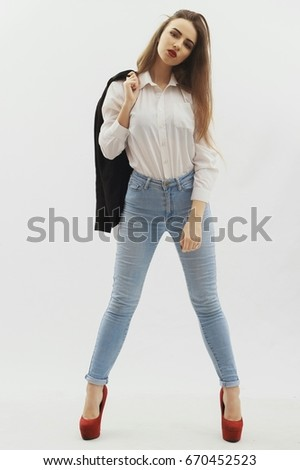 vogue style portrait of beautiful woman in white short and blue jeans on grey background