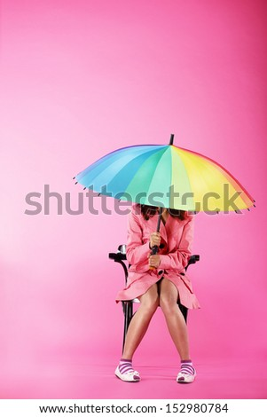 Vogue. Woman in Pink Coat sitting with Colorful Umbrella - stock photo