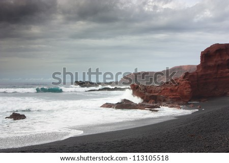 Volcanic beach on overcast day . El Golfo, Lanzarote, Canary Islands, Spain. Black volcanic beach and red giant cliffs under a cloudy sky . - stock photo