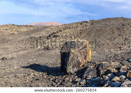 Volcanic bomb in front of volcano Montana Colorada in Lanzarote, Canary Islands, Spain - stock photo