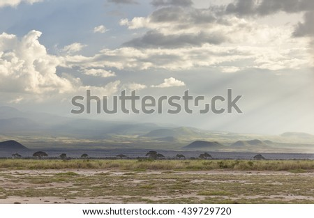 Volcanic craters on the flank of Mount Kilimanjaro seen from Amboseli National Park in Kenya with beautiful evening light. - stock photo