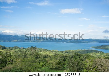Volcanic lagoon Arenal surrounded by lush tropical vegetation, Costa Rica - stock photo