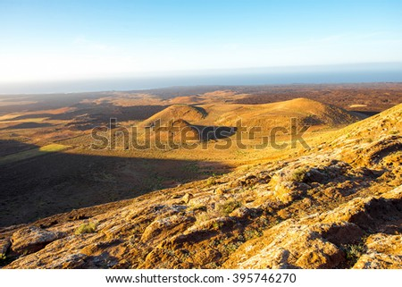 Volcanic landscape view from the top of Caldera Blanca volcano on the sunset on Lanzarote island in Spain