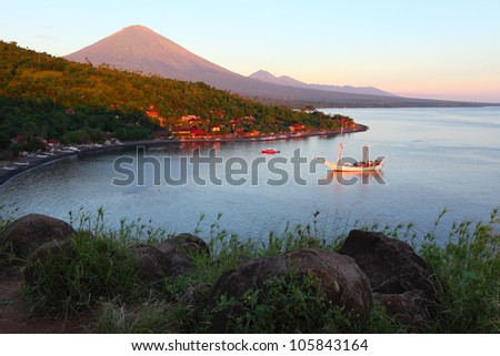 Volcano Agung (Bali, Indonesia) lighted by rising sun and calm lagoon with anchored sail boat - stock photo