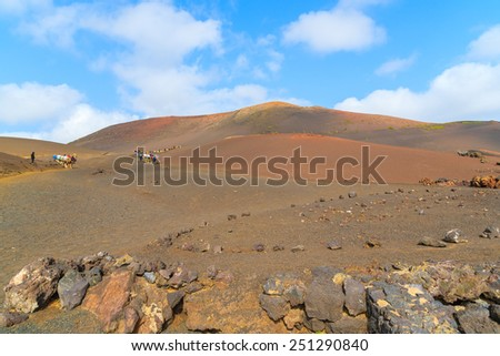 Volcano landscape of Timanfaya National Park with caravans of camels in distance, Lanzarote, Canary Islands, Spain - stock photo