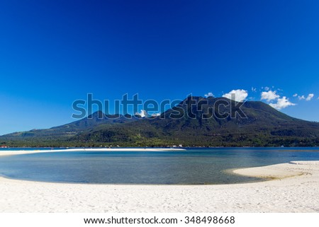 Volcano of mountain tropical island with blue sky clear water and white beach. Philippine paradise. Camiguin - stock photo