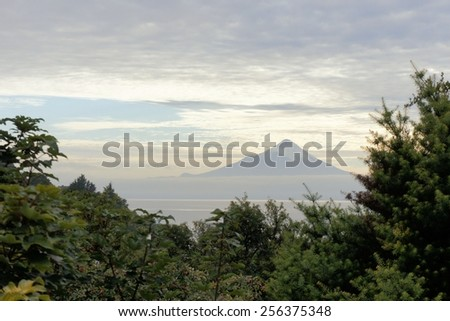 Volcano Osorno with lake Llanquihue in a mist of clouds seen from Puerto Varas, Patagonia, Chile - stock photo