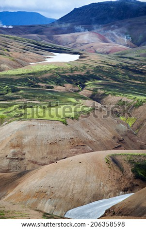 Volcanoes create a bizarre landscape of rhyolite rocks and green moss along the Landmannalaugar trek - stock photo