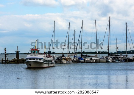 VOLENDAM, NETHERLANDS - JUNE 18, 2014: Boats and sail boats in Volendam Harbour. Volendam - a small town that has preserved the tradition of Dutch fishing villages.