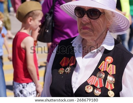VOLGOGRAD, RUSSIA - MAY 9, 2013: A Russian woman wearing Communist Medals participates in a commemorative event remembering the battle of Stalingrad 1942/43. - stock photo