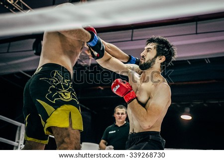 Volgograd, Russia - October 24, 2015: athletes MMA in ring strike each other blows to head during Championship of Russia on mixed martial arts - stock photo
