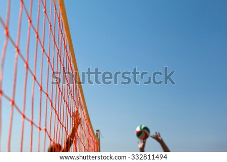 Volleyball Ball Over Net On Background Of Blue Summer Sunny Sky. Ball Flying Through Air On Beach - stock photo