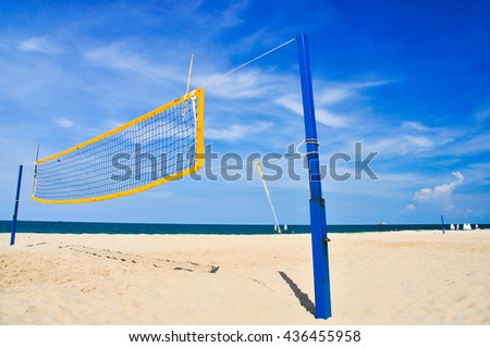 Volleyball net on beach with blue sky and sea, left of frame - stock photo