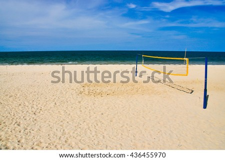 Volleyball net on beach with blue sky and sea, right of frame