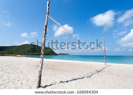 Volleyball net on empty  white sand beach - stock photo