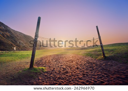 volleyball net on the beach at the sunset - stock photo