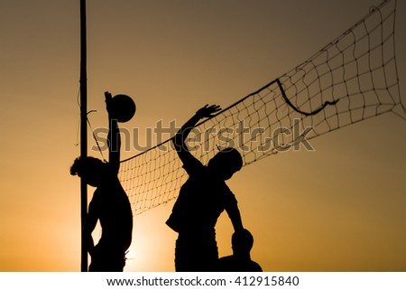 Volleyball playing people silhouettes with vollayball and the net. - stock photo