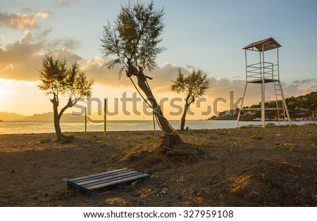 Volleyball tower, net and three trees on sandy beach near the town of Scala, Agistri, Greece