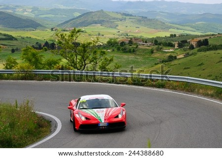 VOLTERRA (PI), ITALY - MAY 17: A red Ferrari 458 Speciale take part to the 1000 Miglia Ferrari Tribute on May 17, 2014 near Volterra (PI). The car has the hood painted with Italian flag colors. - stock photo