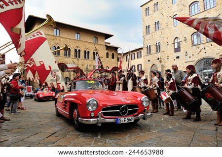 VOLTERRA (PI), ITALY - MAY 17: A red Mercedes 300 SL W 198, followed by a red Maserati 150, takes part to the 1000 Miglia classic car race on May 17, 2014 in Volterra (PI). Both cars were built in 55. - stock photo