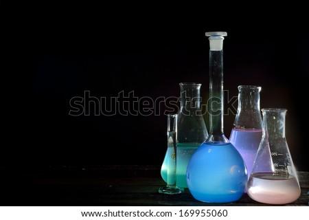 Volumetric laboratory glassware containing colored liquids - stock photo