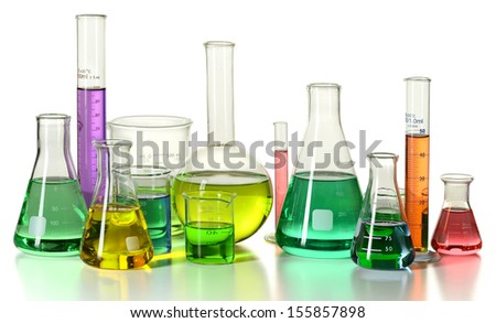 Volumetric laboratory glassware containing colored liquids isolated over white background - With clipping path - stock photo