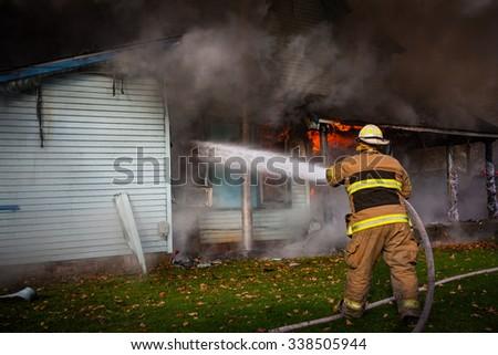 volunteer firefighter spraying water on house  - stock photo