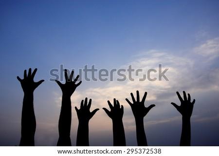 volunteer group raising hands against blue sky background - stock photo