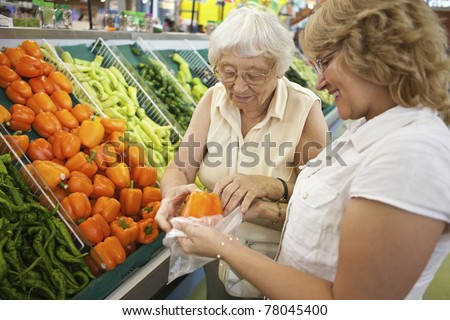 Volunteer helping senior with her shopping - stock photo