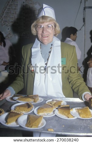 Volunteer serving pumpkin pie at homeless shelter for Christmas, Los Angeles, California - stock photo
