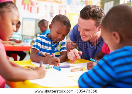 Volunteer teacher helping a class of preschool kids drawing - stock photo