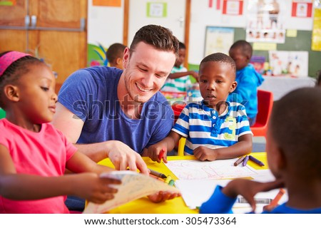 Volunteer teacher sitting with preschool kids in a classroom - stock photo