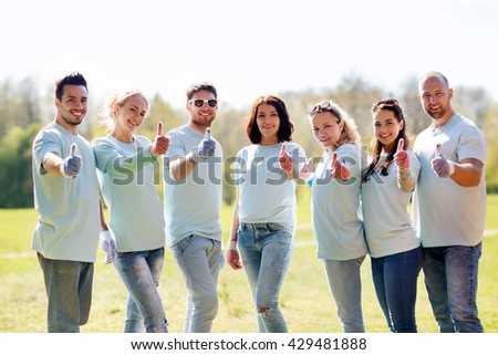 volunteering, charity, people, gesture and ecology concept - group of happy volunteers showing thumbs up in park - stock photo