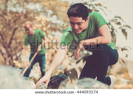 Volunteers picking up litter in the park - stock photo