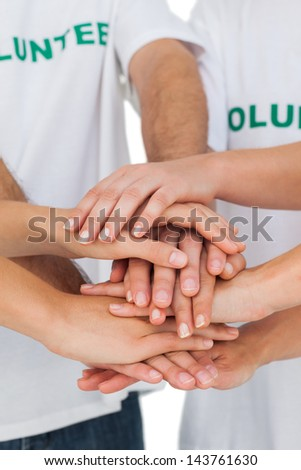 Volunteers putting hands together on white background