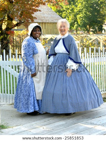 Volunteers re-enact civil war era towns people.  They are wearing costumes and standing on wooden boardwalk in Old Washington State Park. - stock photo
