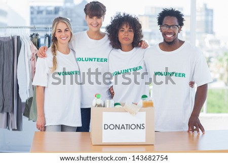 Volunteers standing in front of food in a donation box in their office - stock photo
