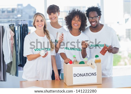 Volunteers taking out food from a donation box in their office - stock photo