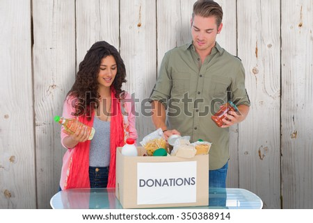 Volunteers taking out food from donations box against wooden background - stock photo