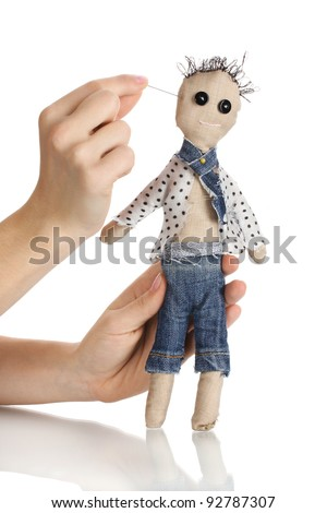 Voodoo doll boy in the hands of women isolated on white - stock photo