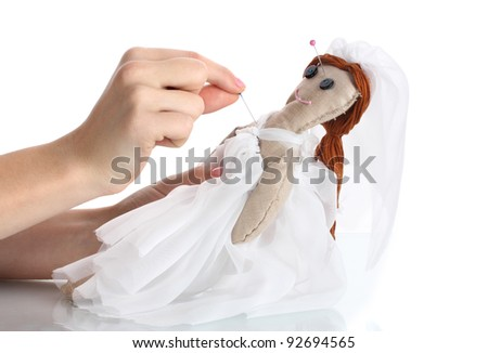 Voodoo doll girl-bride in the hands of women isolated on white - stock photo