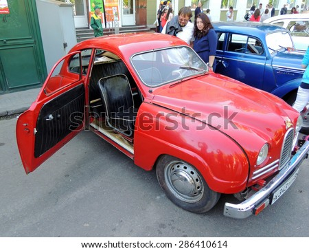 Voronezh, Russia - May 9, 2015: City dwellers look round sweden retro car of 1950s front-wheel drive Saab 93 with open door on the street near city square during the celebration of the Victory V-E Day - stock photo