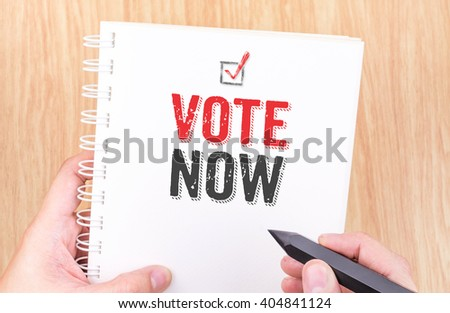 Vote now word on white ring binder notebook with hand holding pencil on wood table,Business concept. - stock photo