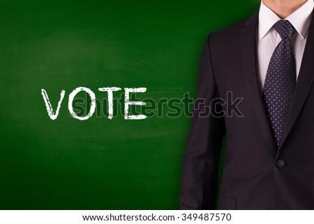 VOTE on Blackboard with businessman - stock photo