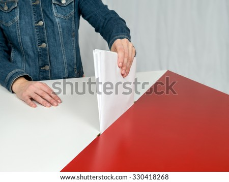 Voter casting a vote into ballot box during election to the Polish Parliament - stock photo