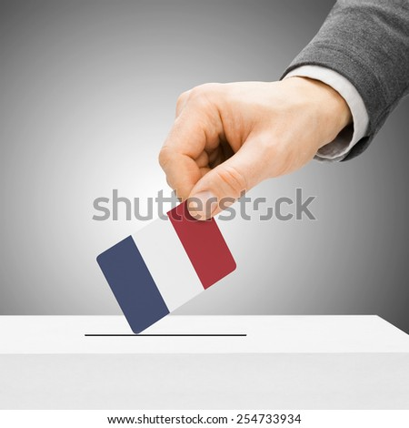 Voting concept - Male inserting flag into ballot box - France - stock photo