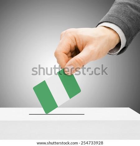 Voting concept - Male inserting flag into ballot box - Nigeria - stock photo
