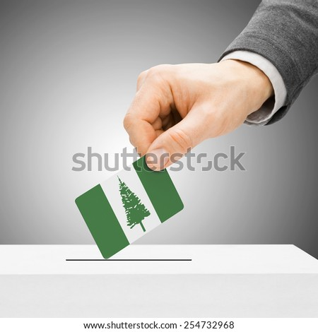 Voting concept - Male inserting flag into ballot box - Territory of Norfolk Island - stock photo